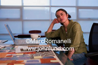 Photo of a woman of mixed race in her office in contemplation. Laptop and cup of coffee on the table in front of her.